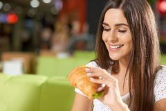 Cheerful young woman enjoying tasty snack in cafe. Cheerful young woman sitting in nice cafe and enjoying tasty snack. Beautiful brunette keeping delicious stock photo