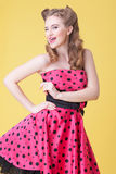Cheerful young woman is expressing positive emotions. Portrait of pin-up girl standing in retro style dress and smiling. She is winking and showing her tongue Stock Images