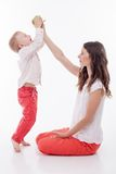 Cheerful young woman is feeding her child Stock Photography