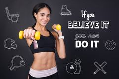 Cheerful young woman feeling confident while exercising with hand weights royalty free stock photos