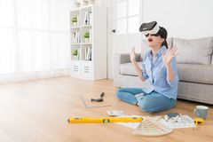 Cheerful woman wearing virtual reality glasses. Cheerful young woman feeling surprised when she wearing virtual reality glasses device viewing 3D simulation Stock Image