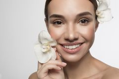 Cheerful young woman with flower is feeling gladness. Fresh as flower concept. Close up portrait of happy attractive naked girl is looking at camera with joy royalty free stock photos