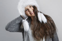 Cheerful young woman in fluffy winter hat Stock Photos