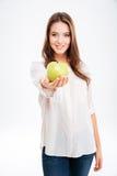 Cheerful young woman giving apple at camera Royalty Free Stock Photos