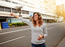 Cheerful young woman hailing a cab on city street. While holding a smart phone - side view Stock Image