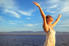 Cheerful young woman with hands up, expressing joy, happiness, freedom standing by the sea Royalty Free Stock Photography