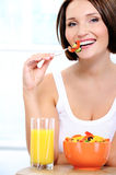 Cheerful young woman has breakfast Royalty Free Stock Photos