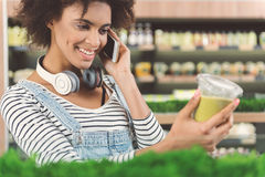 Cheerful young woman is having conversation on smartphone. Always in touch. Charming positive girl is talking on mobile phone with smile while standing in stock photography