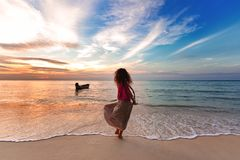 Cheerful young woman having fun on the beach at sunset Royalty Free Stock Photo