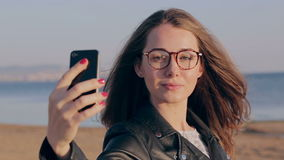 Cheerful young woman having fun taking smartphone selfie pictures of herself on beach. Style girl model wearing fashion stock video