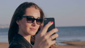 Cheerful young woman having fun taking smartphone selfie pictures of herself on beach. Style girl model wearing fashion stock footage