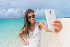 Beach vacation smartphone selfie sunglasses woman. Cheerful young woman having fun taking smartphone selfie pictures of herself on tropical beach travel stock images