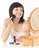Cheerful young woman having make-up wit brush Stock Photo