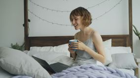 Cheerful young woman having video chat with friends using laptop camera while sitting on bed at home Stock Images