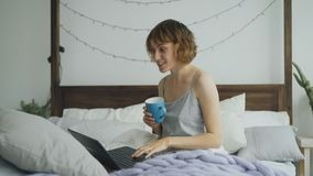 Cheerful young woman having video chat with friends using laptop camera while sitting on bed at home Royalty Free Stock Photos