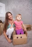 Cheerful young woman with her child are packing Royalty Free Stock Image