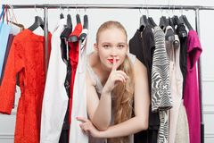 Cheerful young woman is hiding between clothing Royalty Free Stock Images