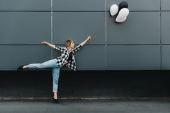 Cheerful young woman holding balloons outdoors. Full length view of cheerful young woman holding balloons outdoors Stock Photo