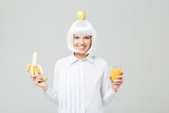 Cheerful young woman holding banana and glass of juice. Cheerful young woman with apple on her head holding banana and glass of juice over white background Stock Photography
