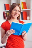 Young woman holding the book and smiling stock photography