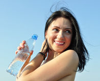 Cheerful young woman holding bottle of cold water Royalty Free Stock Photography