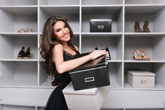 Cheerful young woman holding boxes of shoes in hands, standing in luxury wardrobe, dressing room. She`s happy, smiling. And looking to camera. Wearing nice royalty free stock photography