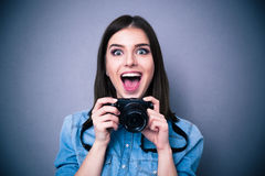 Cheerful young woman holding camera Royalty Free Stock Photo