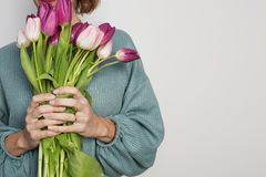 Cheerful young woman holding colored tulips bouquet isolated over gray background. Copy paste space.  stock photography