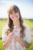 Cheerful young woman holding dandelion Stock Photos