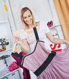 Cheerful young woman holding a dress Stock Image