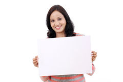 Cheerful young woman holding empty white board. Against white Stock Photography