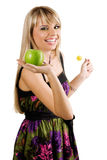 Cheerful young woman holding fresh apple and lolli Royalty Free Stock Images