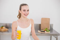 Cheerful young woman holding glass of orange juice Royalty Free Stock Images