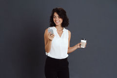 Cheerful young woman holding her phone and coffee in hands Stock Photos