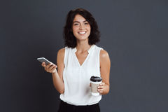 Cheerful young woman holding her phone and coffee in hands Royalty Free Stock Photo