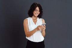 Cheerful young woman holding her phone in hands Stock Image