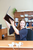 Cheerful young woman holding laptop over head Stock Image