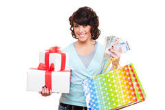Cheerful young woman holding paper money and gifts Royalty Free Stock Photos