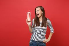 Cheerful young woman holding plastic cup of cola or soda, looking aside, keeping mouth wide open isolated on bright red. Cheerful young woman holding plastic cup royalty free stock photos