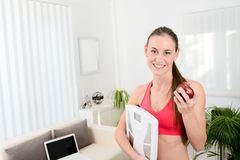 Cheerful young woman holding scales and eating fruit weight loss program Royalty Free Stock Photography
