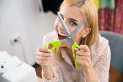 Cheerful young woman holding scissors Stock Photography