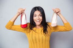 Cheerful young woman holding shoes. Over gray background and looking at camera Stock Photo