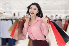 Cheerful young woman holding shopping bag at mall stock photo