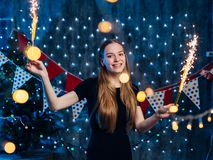 Cheerful young woman holding sparkler in hand. Christmas New Year stock photos