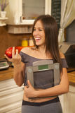 Cheerful young woman holding weight scale and apple. Stock Photo