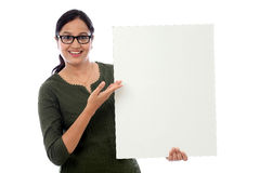 Cheerful young woman holding white board Stock Photos