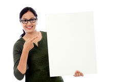 Cheerful young woman holding white board Stock Images