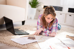 Cheerful young woman at home with laptop computer Stock Images