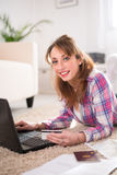 Cheerful young woman at home with laptop computer Stock Photo