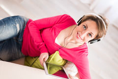 Cheerful young woman at home with tablet compuer Stock Photo